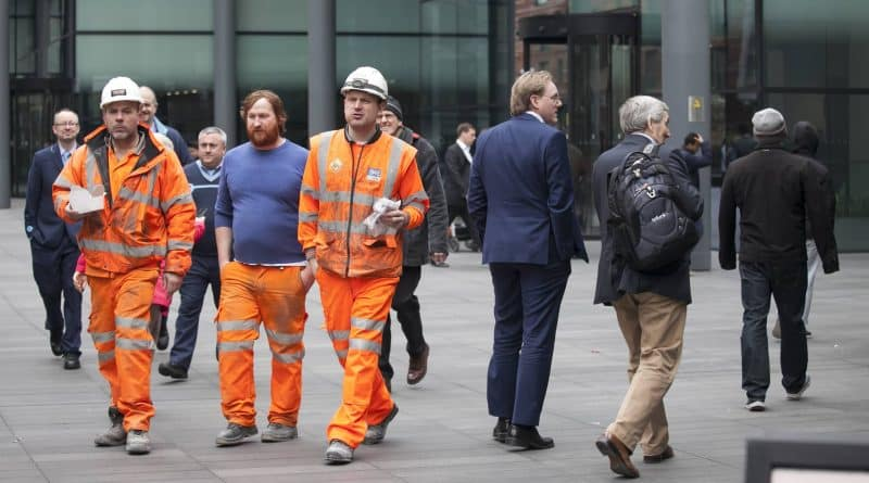 Workers in orange suits with sandwiches go through the Spitalfie