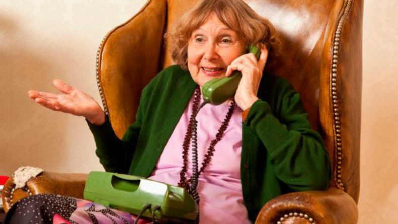A-senior-woman-talking-on-the-phone-in-her-living-room