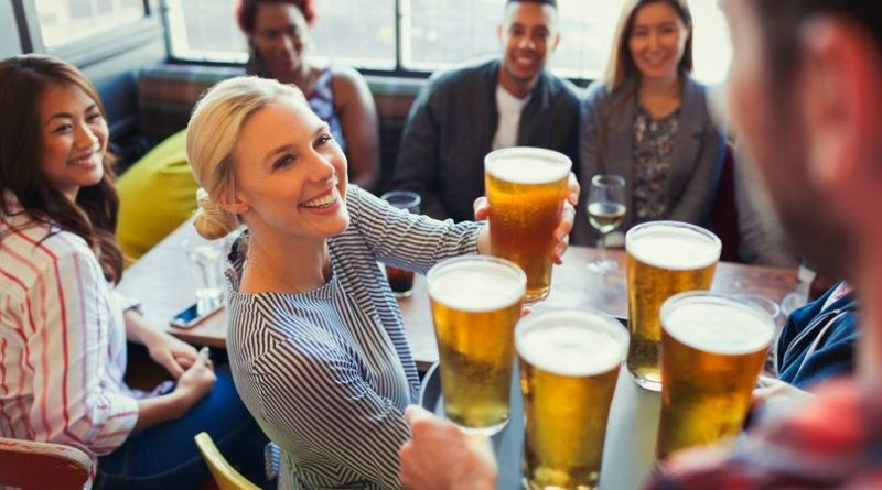 Bartender-serving-beers-on-tray-to-friends-in-bar1