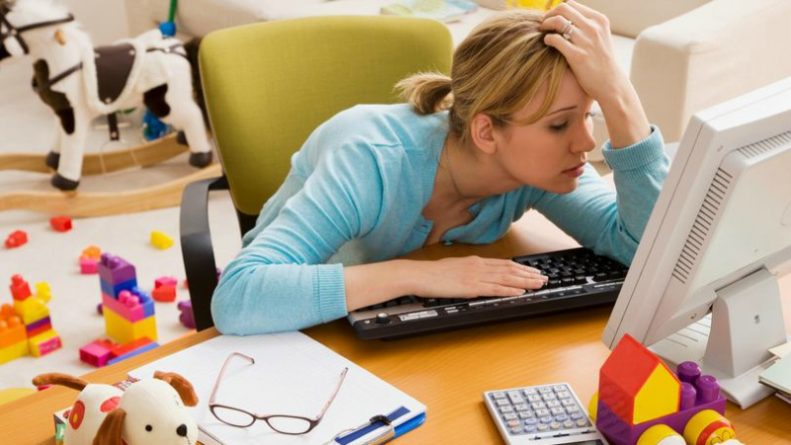 Frustrated-Hispanic-woman-at-desk-surrounded-by-toys
