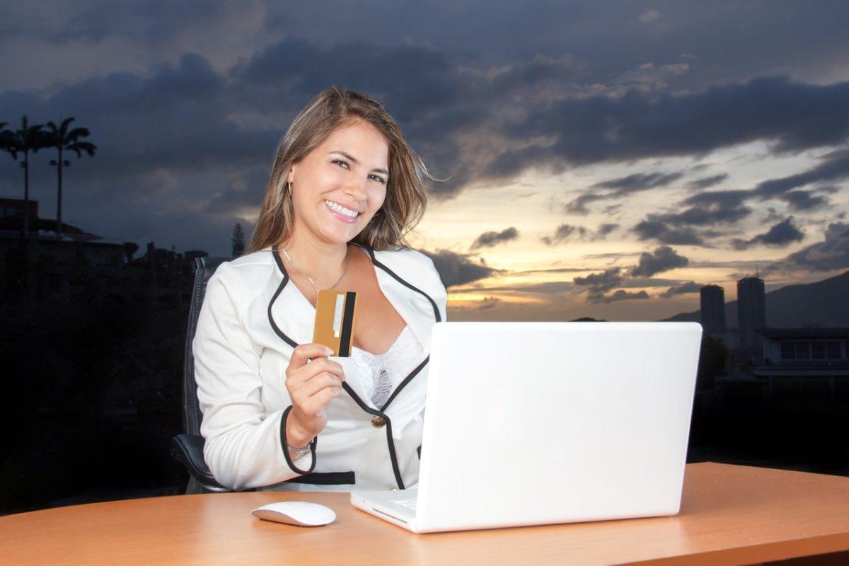 девушка с банковской картой и ноутбуком