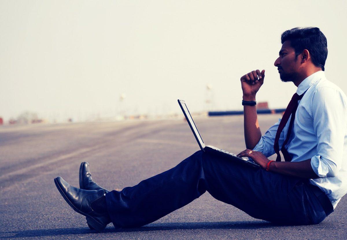 мужчина с ноутбуком на дороге