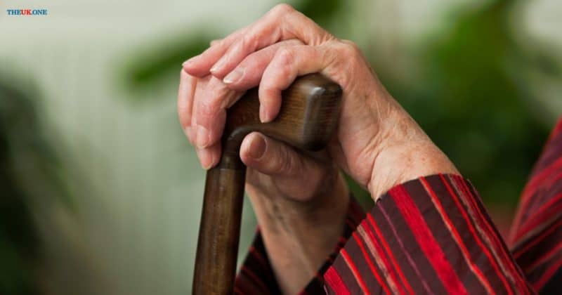 an old woman holding a cane in her hands.